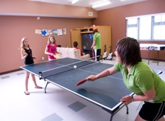Kids play ping pong in a recreation centre
