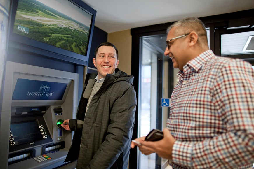 One person at an automatic banking machine, smiling at person standing behind them
