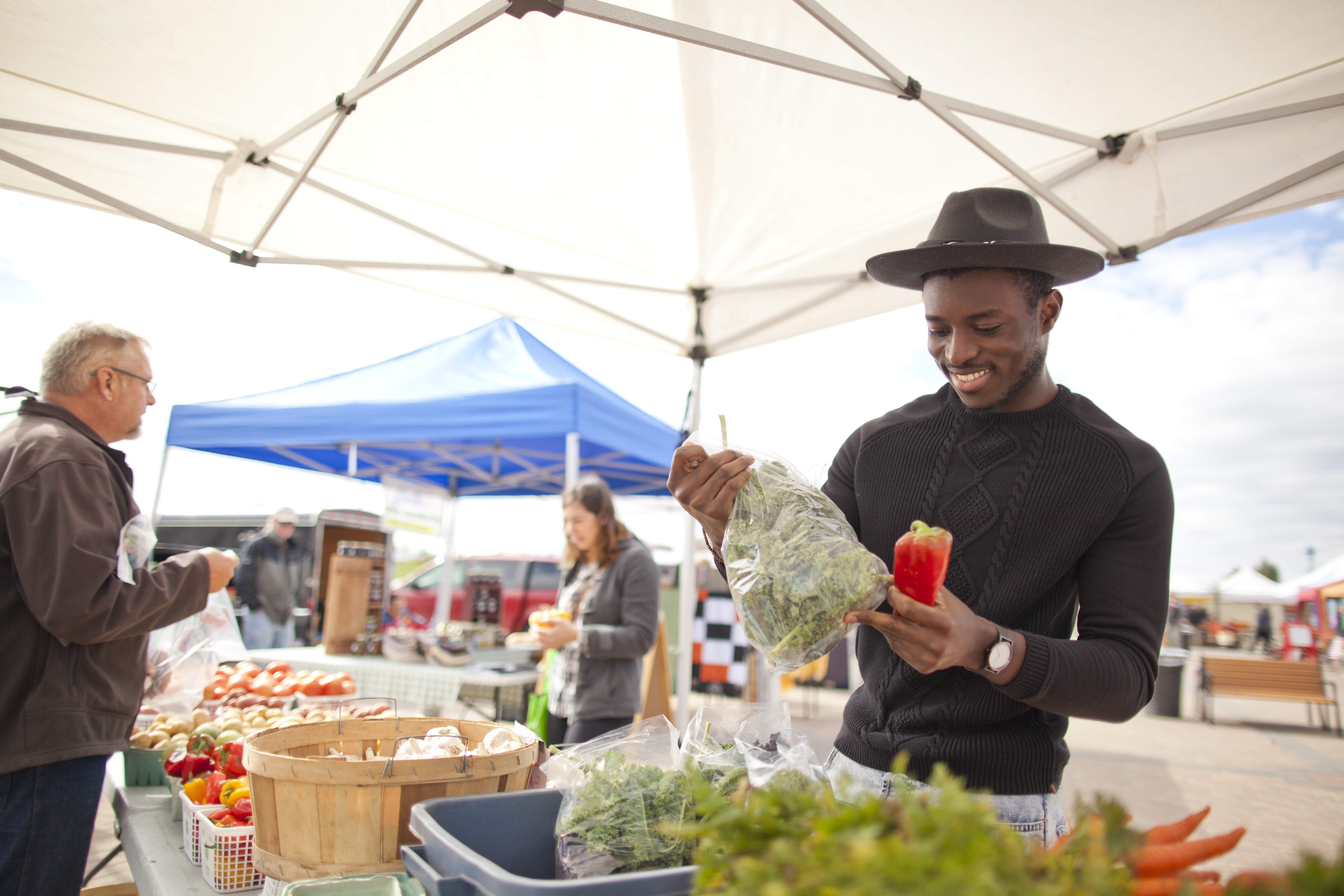A man in a hat looks at produce at the local Farmers Market