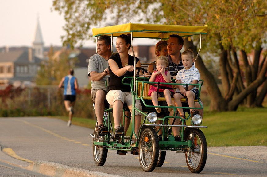 Family riding a 4 person bike