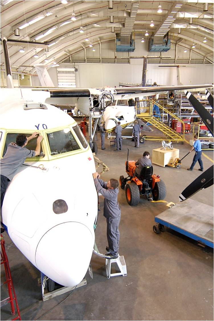 People working in an aircraft maintenance hanger.